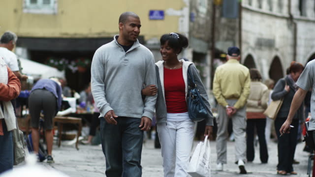 vidéos et rushes de couple walking down a european street holding hands and shopping - se tenir par la main