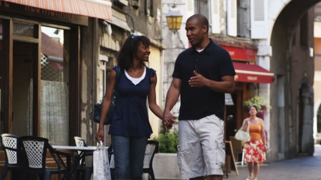 couple walking down a European street holding hands and window shopping