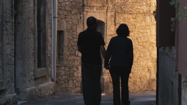 couple walking down a european street - saignon stock videos & royalty-free footage