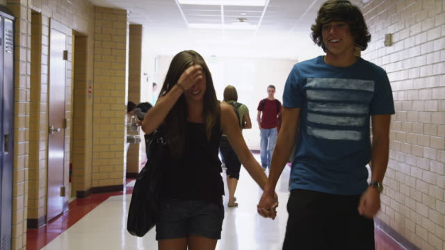 ms couple walking down school corridor / spanish fork city, utah, usa - teenagerpaar stock-videos und b-roll-filmmaterial