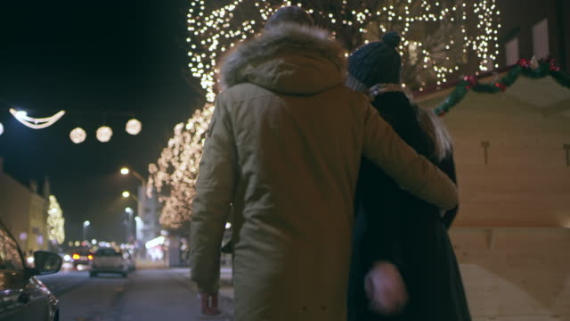 ws couple walking down the city street at christmas time - hugging tree stock videos & royalty-free footage
