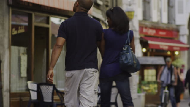 couple walking down the street and man picks up woman, twirls her around and kisses her