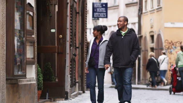 couple walking down the street and stopping to go into a store