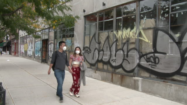 a couple walking hand in hand and wearing protective masks over their nose and mouth walk past several shuttered businesses covered in graffiti on... - scott mcpartland stock videos & royalty-free footage