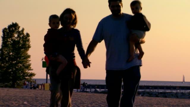 a couple walking hand in hand carrying their children across the beach - gemeinsam gehen stock-videos und b-roll-filmmaterial