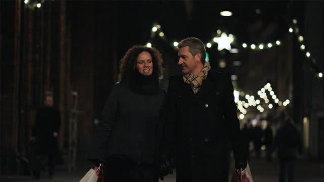 MS Couple walking hand in hand down shopping street / Copenhagen, Denmark