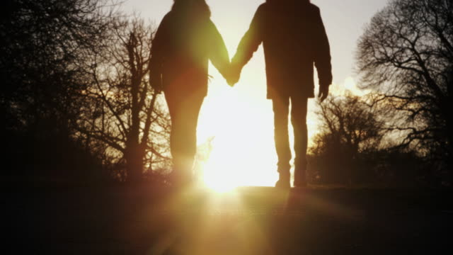 Couple walking holding hands, sunset.