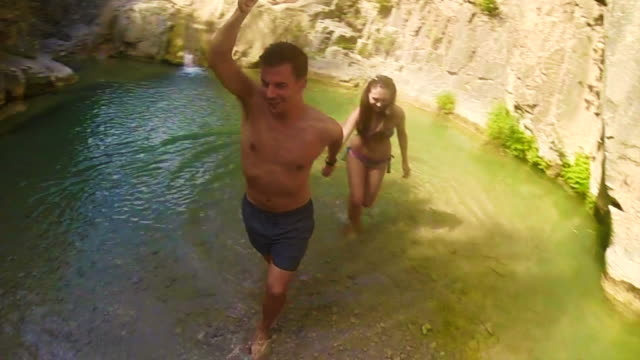 couple walking holding hands with boy leading the way in a beautiful pool river with green waters in the catalan pyrenees on summer time taking a video selfie surrounding him of 360º. - standing water stock videos and b-roll footage