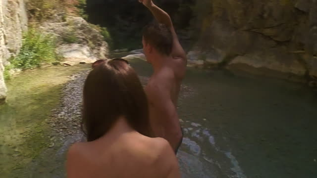 couple walking holding hands with boy leading the way in a beautiful pool river with green waters in the catalan pyrenees on summer time taking a video selfie surrounding him of 360º. - badeshorts stock-videos und b-roll-filmmaterial