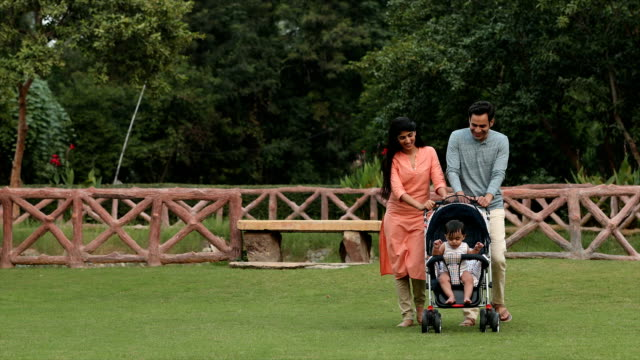 MS ZI Couple walking in backyard with their baby boy sitting in pram / Delhi, India