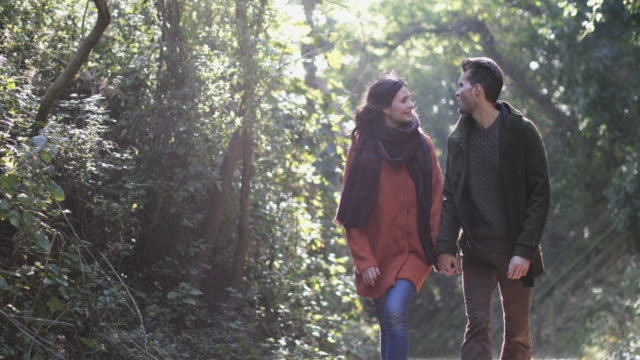 couple walking in forest in fall - オーバーコート点の映像素材/bロール