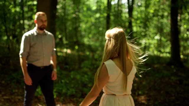 MEDIUM SHOT DOLLY SHOT Couple walking in forest on sunny day
