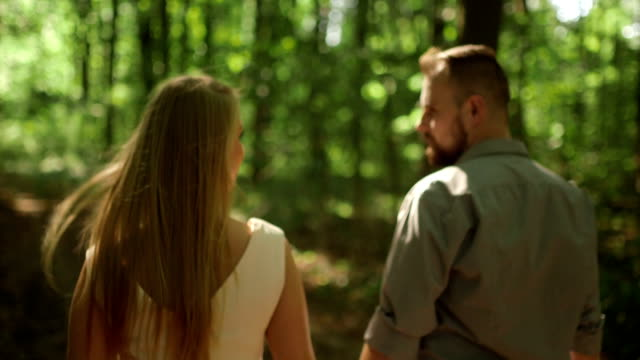 MEDIUM SHOT TRACKING SHOT TILT DOWN Couple walking in forest on sunny day