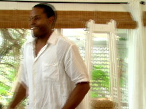 vidéos et rushes de ms,  couple walking in living room,  man sitting on sofa,  harbour island,  bahamas - se mordre les lèvres