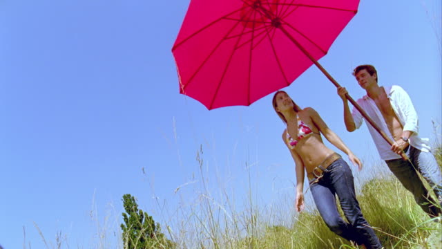 slo mo, ms, canted, couple walking in meadow, man carrying large pink sun umbrella, saint ferme, gironde, france - bikinioberteil stock-videos und b-roll-filmmaterial