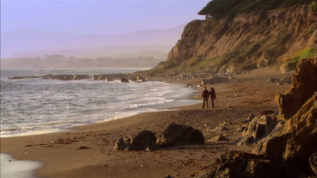 ws, couple walking in moonstone beach, cambria, california, usa - boulder rock stock videos and b-roll footage