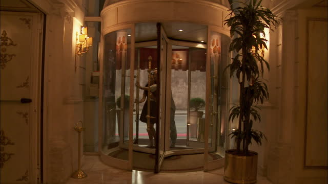 MS Couple walking into hotel lobby through revolving door, Rome, Italy