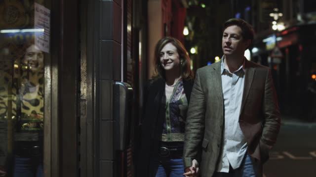 ms couple walking into store at night / soho, london, uk - human settlement stock videos & royalty-free footage