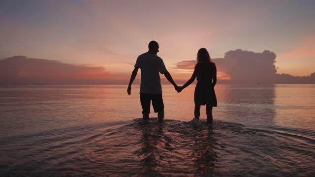 coppia che cammina in mare al tramonto - controluce video stock e b–roll