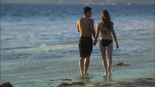vidéos et rushes de slo mo ws couple walking near water's edge along beach / vista del mar, california, usa - mar