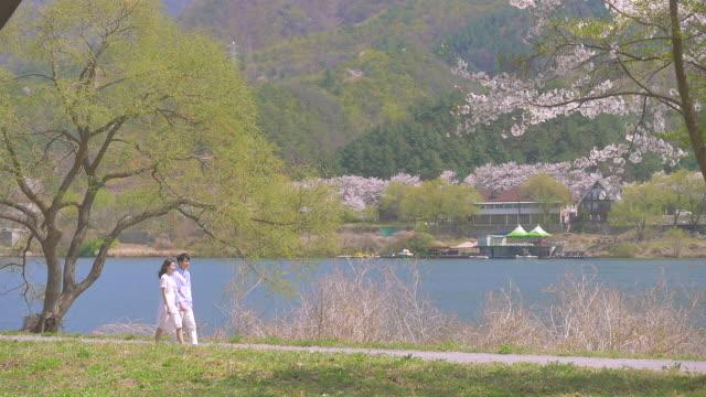 a couple walking next to the riverside - 年の差カップル点の映像素材/bロール