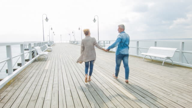 couple walking on a jetty - molo video stock e b–roll