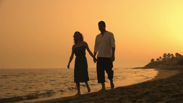 Couple walking on beach at dusk/Marbella region, Spain