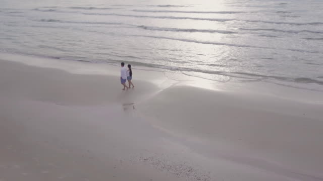 Couple walking on beach at sunset at  Petchaburi, Thailand