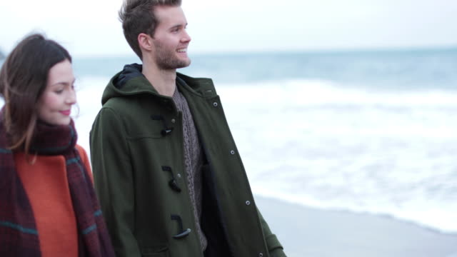 Couple walking on beach in Winter