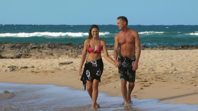 couple walking on beach smiling and holding hands - see other clips from this shoot 1142 stock videos & royalty-free footage