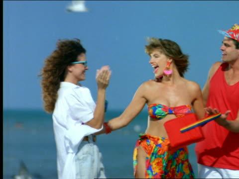 stockvideo's en b-roll-footage met couple walking on beach toward camera other woman walks in - man met een groep vrouwen