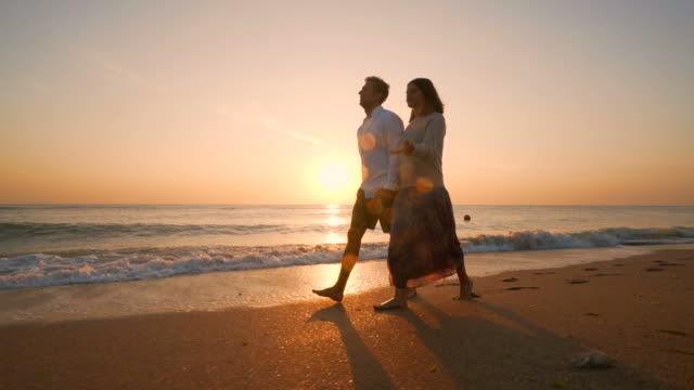 couple walking on beach. - riva dell'acqua video stock e b–roll