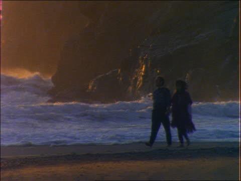 stockvideo's en b-roll-footage met couple walking on beach / waves in background - zij aan zij