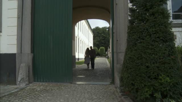 ws couple walking on cobble stone footpath through gate, brussels, belgium - kullersten bildbanksvideor och videomaterial från bakom kulisserna