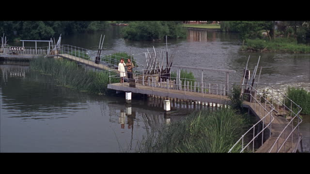 WS PAN Couple walking on crook walkway across park river