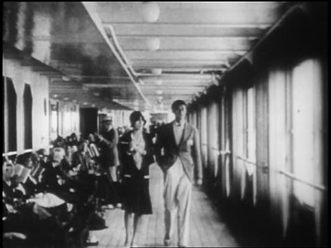 B/W 1928 couple walking on deck of ocean liner past passengers seated on deck chairs / newsreel