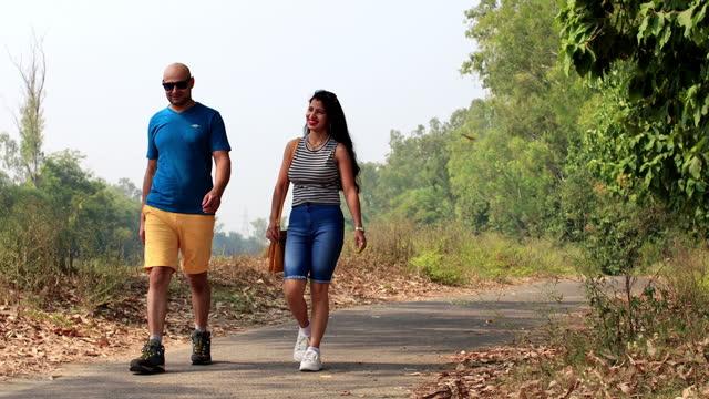 vídeos y material grabado en eventos de stock de pareja caminando por el camino vacío - pantalón corto