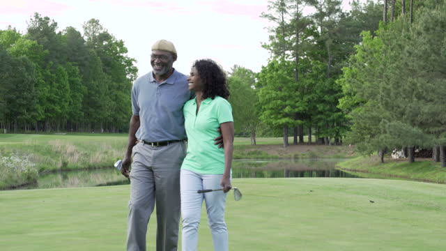 couple walking on golf course - golfer stock videos and b-roll footage