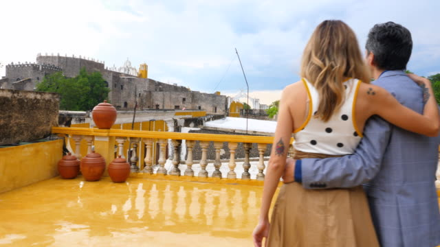 stockvideo's en b-roll-footage met ts couple walking on hotel rooftop deck over looking city of izamal - mid volwassen koppel