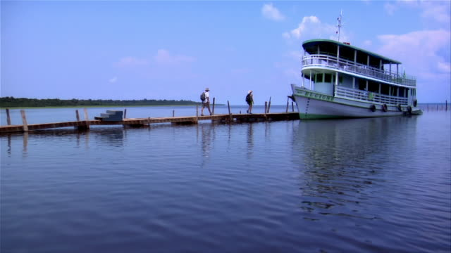 couple walking on jetty towards moored ferry boat / the amazon, brazil - paar mittleren alters stock-videos und b-roll-filmmaterial