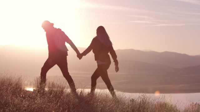 couple walking on mountain top holding hands - back lit stock videos and b-roll footage