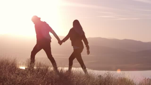 vídeos de stock, filmes e b-roll de couple walking on mountain top holding hands - contraluz