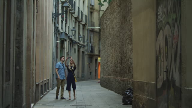 couple walking on narrow sidewalk photographing architecture / barcelona, barcelona, spain - street stock videos & royalty-free footage