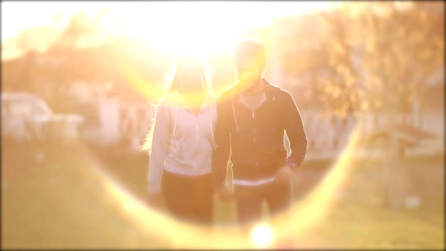 Couple walking on park with lens flare