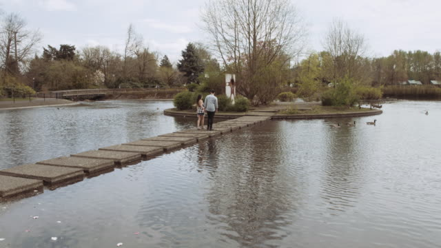 Couple walking on path through a pond