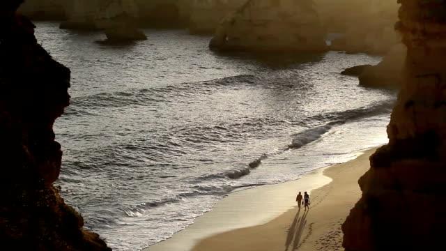 ws ha couple walking on praia da marinha at sunset / algarve, portugal - impronta del piede video stock e b–roll