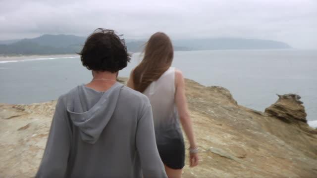 ws ts couple walking on ridge with sea in background / cape kiwanda, oregon, usa - langes haar stock-videos und b-roll-filmmaterial