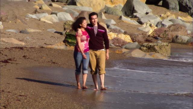 MS, PAN, Couple walking on rocky beach, Moonstone Beach, Cambria, California, USA