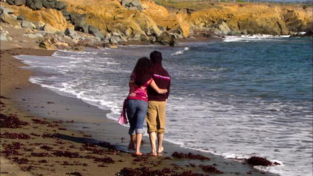 MS, Couple walking on rocky beach, rear view, Moonstone Beach, Cambria, California, USA