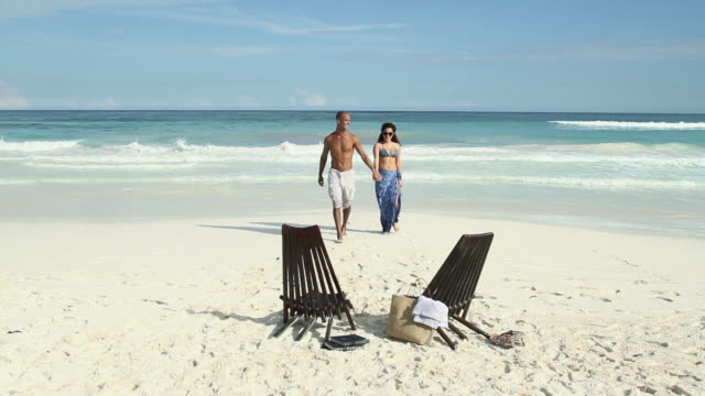 couple walking on sandy beach and sitting on deck chairs - sarong stock videos & royalty-free footage